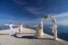 De jonggehuwden stellen dichtbij de huwelijksboog Royalty-vrije Stock Foto's