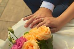 De jonggehuwden tonen hun handen met trouwringen Stock Fotografie