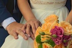 De jonggehuwden tonen hun handen met trouwringen Royalty-vrije Stock Afbeeldingen