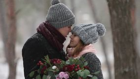 De jonggehuwden verzorgen en de kus van de bruidomhelzing en verwarmen elkaar in sneeuwpijnboombos tijdens sneeuwval in langzame  stock footage