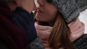 De jonggehuwden verzorgen en de kus van de bruidomhelzing en verwarmen elkaar in sneeuwpijnboombos tijdens sneeuwval in langzame  stock videobeelden