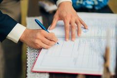 De jonggehuwden zetten hun handtekeningen in de handeling van het registreren van een huwelijk stock fotografie