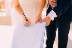 De jonggehuwden zetten hun handtekeningen in de handeling van het registreren van een huwelijk stock afbeeldingen