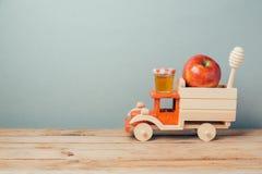 De Joodse achtergrond van vakantierosh Hashana met stuk speelgoed vrachtwagen, honing en appelen royalty-vrije stock afbeeldingen