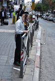De Joodse jongen lijmt advertentie in Jeruzalem stock foto