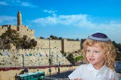 De Joodse kleine jongen bevindt zich tegen kasteelmuren van Jeruzalem Stock Foto