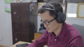 De journalist in de hoofdtelefoons schrijft de tekst voor videonews stock footage