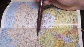 De juiste man plaatsen van het handonderzoek op Russische document aardrijkskunde brengen door een pen in kaart Sluit omhoog stock video