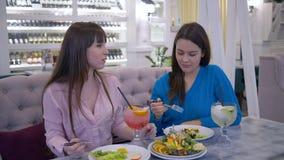 De juiste voeding, meisjes tijdens het dieet eet fruit en drank verse sapzitting bij lijst in koffie stock footage