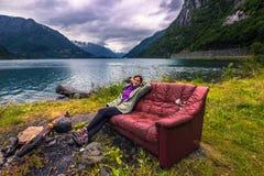 21 de julho de 2015: Viajante que relaxa em um sofá vermelho no norwegia fotos de stock