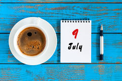 9 de julho Dia 9 do mês, calendário no fundo de madeira azul da tabela com o copo de café da manhã Conceito do verão Fotografia de Stock Royalty Free