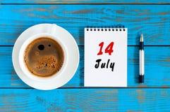 14 de julho Dia 14 do mês, calendário no fundo de madeira azul da tabela com o copo de café da manhã Conceito do verão Fotos de Stock Royalty Free
