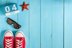 4 de julho Imagem do calendário de madeira da cor do 4 de julho no fundo azul Árvore no campo Espaço vazio para o texto Fundo do  Imagem de Stock Royalty Free