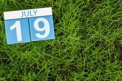 19 de julho Imagem do calendário de madeira da cor do 19 de julho no fundo do gramado dos greengrass Dia de verão, espaço vazio p Imagens de Stock