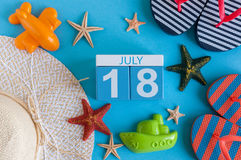 18 de julho Imagem do calendário do 18 de julho com os acessórios da praia do verão e o equipamento do viajante no fundo Árvore n Foto de Stock