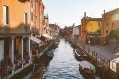 22 de julho de 2013 o por do sol pitoresco de Veneza Itália sobre o canal com os barcos entre casas coloridas velhas apedreja rua Fotografia de Stock