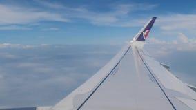 2 de julio de 2018 China, Macao Vista del ala del aeroplano a través de la ventana plana, de las nubes y del cielo azul almacen de metraje de vídeo