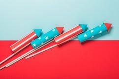 4 de julio, cohetes para los fuegos artificiales en un fondo rojo azul con el espacio para el texto en el estilo de minimalismo fotos de archivo