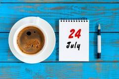 24 de julio Día 24 del mes, calendario en fondo de madera azul de la tabla con la taza de café de la mañana Concepto del verano Foto de archivo
