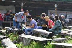11 DE JULIO DE 2013 - GARANA, RUMANIA Escenas y gente que se sientan o que caminan en la calle en un día lluvioso Imagen de archivo