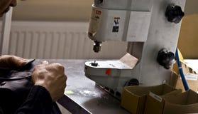 21 de julio de 2017: Un hombre cose los botones a la ropa en una fábrica de costura en la ciudad ucraniana de Balta Foto de archivo libre de regalías