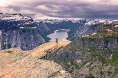 22 de julio de 2015: Viajero en el borde de Trolltunga, Noruega Imagen de archivo libre de regalías