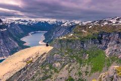22 de julio de 2015: Viajero en el borde de Trolltunga, Noruega Foto de archivo libre de regalías