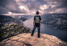 20 de julio de 2015: Viajero en la cumbre de la roca del púlpito, Noruega Foto de archivo libre de regalías
