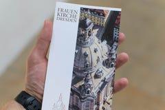 20 de julio de 2007 Dresden Iglesia de Alemania del Frauenkirche Una postal con la historia de la iglesia en las manos foto de archivo libre de regalías