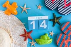 14 de julio Imagen del calendario del 14 de julio con los accesorios de la playa del verano y el equipo del viajero en fondo Árbo Imagen de archivo libre de regalías