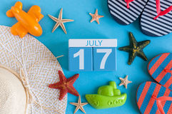 17 de julio Imagen del calendario del 17 de julio con los accesorios de la playa del verano y el equipo del viajero en fondo Árbo Imagenes de archivo