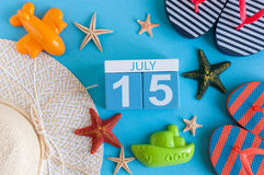 15 de julio Imagen del calendario del 15 de julio con los accesorios de la playa del verano y el equipo del viajero en fondo Árbo Fotografía de archivo