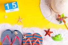 15 de julio Imagen del calendario del 15 de julio con los accesorios de la playa del verano y el equipo del viajero en fondo Árbo Imagen de archivo