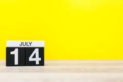 14 de julio Imagen del 14 de julio, calendario en fondo amarillo Adultos jovenes Con el espacio vacío para el texto Imágenes de archivo libres de regalías