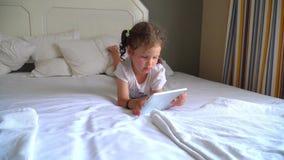 3 de julio de 2017 Turquía Alania hotel La niña juega en la cama en la tableta almacen de video