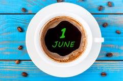 1º de junho dia do mês 1, calendário diário escrito no copo de café da manhã no fundo de madeira azul Conceito do verão Fotos de Stock Royalty Free