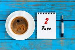 2 de junho Dia do mês 2, calendário diário perto do copo de café da manhã no fundo de madeira azul Conceito do verão, parte super Foto de Stock Royalty Free