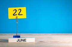 22 de junho Dia 22 do mês de junho, calendário na tabela com fundo azul Horas de verão, espaço vazio para o texto ou molde imagem de stock
