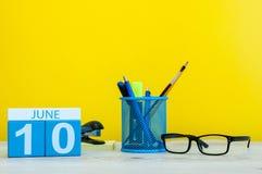 10 de junho Dia 10 do mês, calendário no fundo amarelo com suplies do escritório Horas de verão no trabalho Fotos de Stock Royalty Free