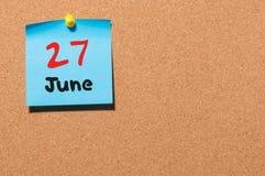 27 de junio Día 27 del mes, calendario de la etiqueta engomada del color en tablón de anuncios Adultos jovenes Espacio vacío para Imagen de archivo