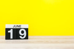 19 de junio Día 19 del mes, calendario en fondo amarillo Árbol en campo Espacio vacío para el texto Foto de archivo