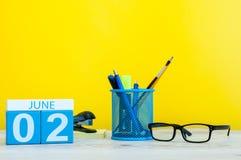 2 de junio Día 2 del mes, calendario en fondo amarillo con los suplies de la oficina Día de verano, espacio vacío para el texto Imágenes de archivo libres de regalías