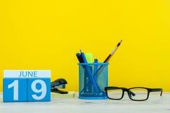 19 de junio Día 19 del mes, calendario en fondo amarillo con los suplies de la oficina Tiempo de verano en el trabajo Fotos de archivo libres de regalías