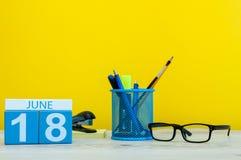 18 de junio Día 18 del mes, calendario en fondo amarillo con los suplies de la oficina Tiempo de verano en el trabajo Foto de archivo libre de regalías