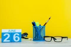 26 de junio Día 26 del mes, calendario en fondo amarillo con los suplies de la oficina Tiempo de verano en el trabajo Día interna Foto de archivo libre de regalías
