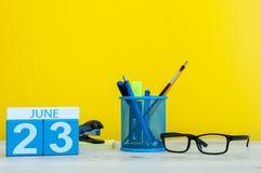23 de junio Día 23 del mes, calendario en fondo amarillo con los suplies de la oficina Tiempo de verano en el trabajo internacion Fotos de archivo