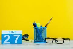 27 de junio Día 27 del mes, calendario en fondo amarillo con los suplies de la oficina Tiempo de verano en el trabajo internacion Fotos de archivo libres de regalías