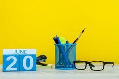 20 de junio Día 20 del mes, calendario en fondo amarillo con los suplies de la oficina Tiempo de verano en el trabajo Paseo para  Imagenes de archivo