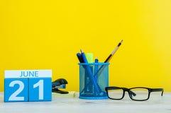 21 de junio día 21 del mes, calendario en fondo amarillo con los suplies de la oficina Tiempo de verano en el trabajo Va el día q Imagen de archivo libre de regalías