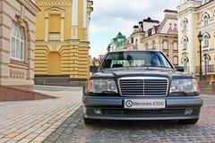 12 de junio de 2011, Kiev - Ucrania Lobo de Mercedes E500 W124 en el fondo de casas viejas hermosas fotos de archivo libres de regalías